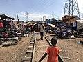 A boy walks along the train tracks at one of the markets that are along the train tracks of the train in Kampala, Uganda.jpg