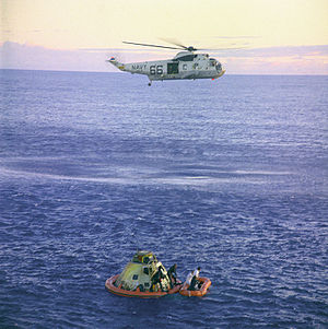 Photograph of a helicopter hovering above ocean with the Apollo 10 capsule and astronauts floating nearby