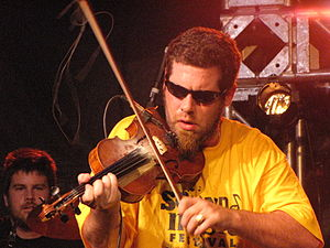 Ashley MacIsaac - MacIsaac performing at the Burlington Sound of Music festival in 2010. Neil MacIntosh also pictured on drums.