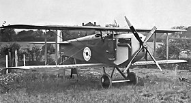 Three-quarter front view of biplane with four-bladed propeller, parked in a field