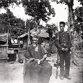 Bai Bureh - Bai Bureh seen here in 1898 in Kasseh, sitting relaxed in his traditional dress with a handkerchief in his hands, while a guard stands next to him