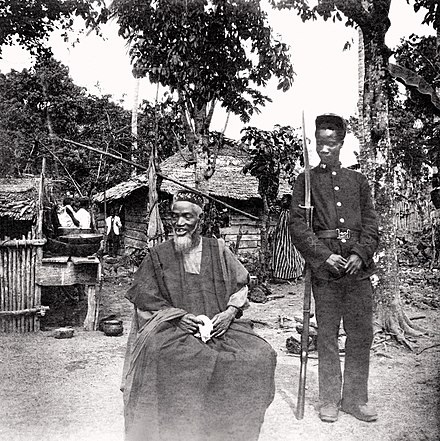Temne leader Bai Bureh seen here in 1898 after his surrender, sitting relaxed in his traditional dress with a handkerchief in his hands, while a Sierra Leonean Royal West African Frontier soldier stands guard next to him Bai Bureh (1898).jpg