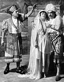 Three figures in exotic costumes; to the right a man and a woman embrace, while on the left another man addresses them, left arm raised perhaps in a gesture of blessing