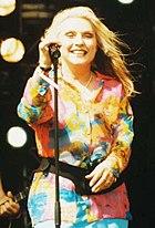 Debbie Harry hält ein stehendes Mikrofon