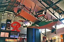 The Boeing B-1 on display in the museum's Grand Atrium, with the Rainier Brewing Company logo sign behind.