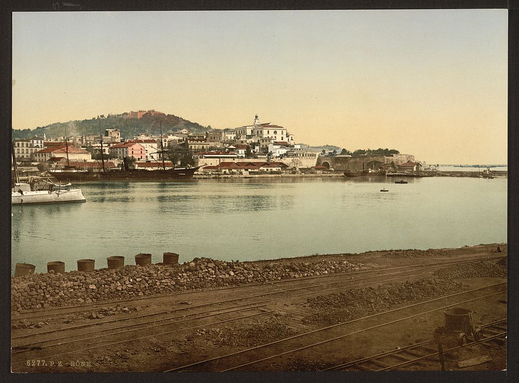 Colourised photo print of the quayside at Bona in Algeria in the year 1899. The foreground of the picture comprises the quay itself, with the centre of the picture containing a sea inlet or the mouth of a river. In the background is the port itself sloping up a hillside, with ships of various sizes moored before it