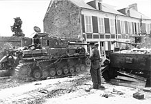 Two tanks are positioned on either side of a street with a soldier standing in the middle of the road; the road is damaged and scattered with debris.