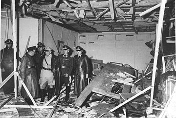 A black-and-white photograph of six men in military uniforms while surveying a shattered conference building.