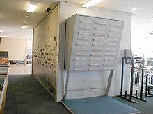 Une face de la structure avec des prises d'escalade et une seconde face avec un pan inclinée sur lequel sont fixées des réglettes en bois