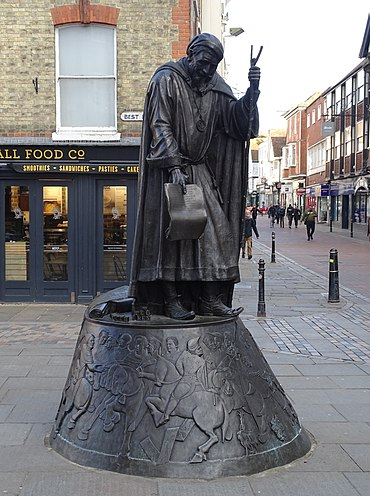 Statue of Geoffrey Chaucer, dressed as a Canterbury pilgrim, on the corner of Best Lane and the High Street, Canterbury