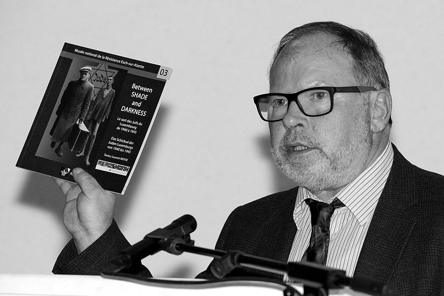 Am Kader vun der Wanderausstellung «Between Shade and Darkness. Le sort des Juifs du Luxembourg de 1940 à 1945», hat d'Gemeng Reckeng op der Mess, zesumme mat der asbl MemoShoah Lëtzebuerg, fir den 31. Mäerz 2015 op en Debat iwwer de Rapport vum Historiker Vincent Artuso zu der «Kollaboratioun vun der Lëtzebuerger Verwaltungskommissioun mat Nazi-Däitschland», invitéiert.Mam Vincent Artuso hunn diskutéiert de fréiere Minister an Auteur vum Buch Luxemburg im Wandel der Zeiten, Erinnerungen (1927-2014), Jean Hamilius, als Zäitzeien, an den Henri Juda, President vu MemoShoah Lëtzebuerg. D'Danielle Schumacher, Journalistin beim Lëtzebuerger Wort, huet d'Diskussioun moderéiert. De Carlo Muller, Buergermeeschter vu Reckeng, bei senger Schlussried.