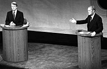 A monochrome picture of Carter and Ford, both standing at podiums during a debate.