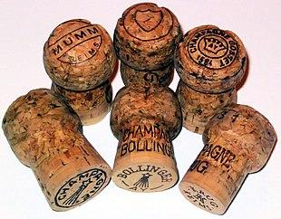 Tappi di champagne di varie marche. Il tappo centrale, nella fila superiore, appartiene ad una bottiglia di Dom Pérignon.
