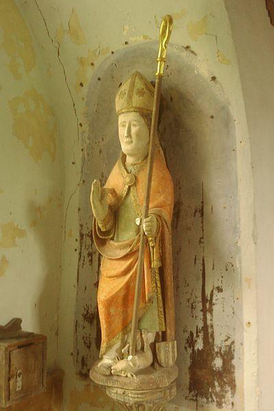 Statue de Saint Loup, évèque de Bayeux, terrassant un loup. Pierre polychromée du XVIe, La Chapelle Heuzebrocq, fr:Beuvrigny