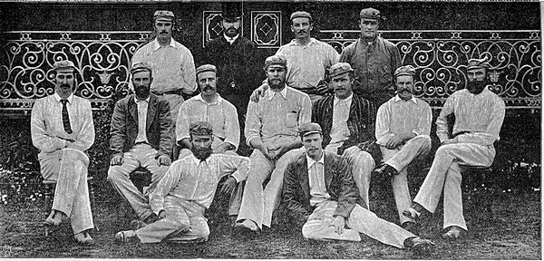 13 men dressed in cricket clothing posing for a group photograph. Three rows.