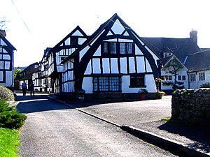 "Timber framing - A ""true"" or ""full"" cruck half-timbered building in Weobley, Herefordshire, England: The cruck blades are the tall, curved timbers which extend from near the ground to the ridge."