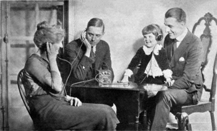 Family listening to the first radio broadcasts on a crystal radio in 1922. Since crystal radios cannot drive loudspeakers they must share earphones. Crystal radio advertisement.png