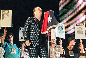 """A light-skinned man with brown hair singing into a microphone on a stand, which has a flag draped over it. His shirt and trousers are both grey and feature a design of many overlapping circles. He faces to the right. A line of women stand behind him, each one holding up a sign that says """"Donde Estan"""" or """"Justcia"""". Every sign has an image of a different person below the text."""