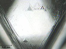 One face of an uncut octahedral diamond, showing trigons (of positive and negative relief) formed by natural chemical etching Diamond face trigons scale.jpg