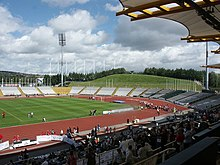Interior of a sports stadium. There is a running track surrounding a central grassed area. In the distance there are the outer stands. In the foreground is the main stand, with plenty of people seated