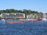 Drachenboote mit kontrastreichem Klarschiff-Bau im Hintergrund (Flensburg 2013).JPG
