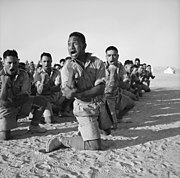 A squad of men kneel in the desert sand while performing a war dance