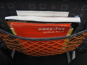 Airline seat - Seat pocket containing safety card, magazines, and airsickness bag.