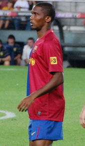A black man wearing a blue-and-red halved shirt and blue shorts.