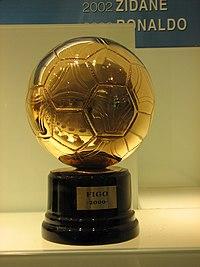 Portrait d'un trophée dorée en forme de ballon avec un support noir
