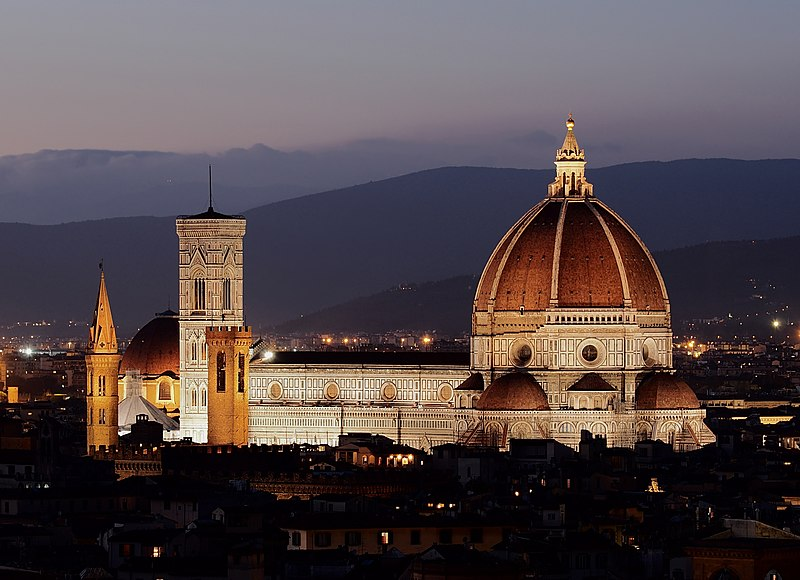 The Cathedral of Saint Mary of the Flower, illuminated at night, showing the large red brick dome, a decorated white marble nave, and a vertical, white marble bell tower to the left. Mountains are visible in the background and a dark, low-lying city in the foreground.