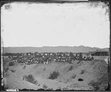 A black and white photograph showing a group of approximately 150 Native Americans in European clothing standing at the slope of a ditch with an arid desert landscape in the background