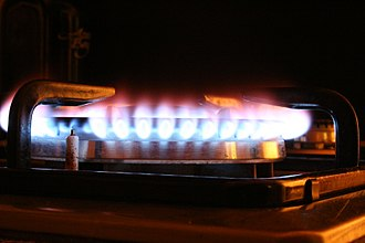 Electric spark - Gas stove burner - the electric spark flame igniter is shown at the left.