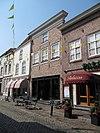 foto van Huis met schilddak en gebosseerd grijsgepleisterde lijstgevel, vensters en winkelpui