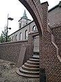 Ingelmunster, gerestaureerde kasteelmuur en Sint-Amandskerk.jpg