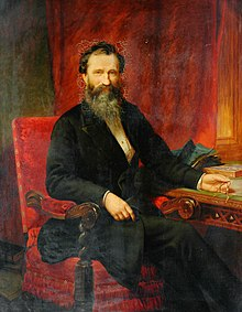 Portrait of bearded man (Isaac Holden) sat at a desk