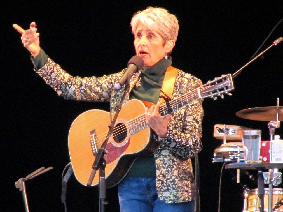 Baez holds guitar, in blue jeans, brown mock turtleneck, patterned jacket, black backdrop, talking and gesturing
