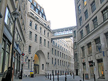 A narrow road with tall buildings of grey stone on both sides. The building on the left has a large entrance archway.