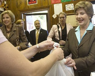 Betsy DeVos - DeVos (far left) watches First Lady Laura Bush (far right)  making a purchase at Franklin Cider Mill. Bush was in Michigan to support DeVos's husband in his gubernatorial campaign.