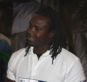 A black man with dreadlocks wearing a white polo shirt. He is smiling and facing left.