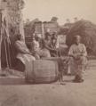 Little Bo Peep. Group of men and women seated outside, child peeking out of a barrel in the foreground.png