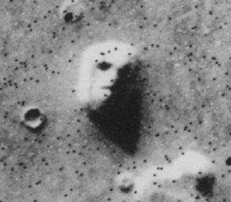 "Pareidolia - Satellite photo of a mesa in the Cydonia region of Mars, often called the ""Face on Mars"" and cited as evidence of extraterrestrial habitation. Subsequent higher-resolution photos from multiple viewpoints demonstrated that the ""face"" is in fact a natural rock formation."