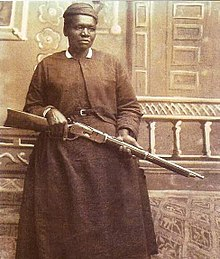 Sepia-tone photograph of Mary Fields, holding a rifle