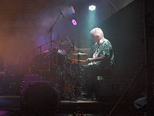 A man with gray hair drums behind his drum-set in a faintly lit room.