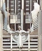 Una figura estilizada de un ser humano masculino con los brazos extendidos y la cabeza ligeramente inclinada hacia adelante, con un casco alado y con cresta, montado en la fachada de un edificio.