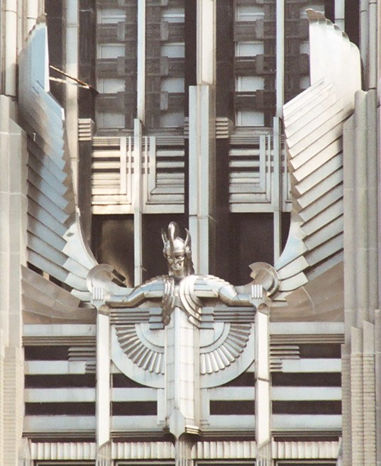 A stylized figure of a male human with outstretched arms and head tilted slightly forward, wearing a winged and crested helmet, mounted on the facade of a building