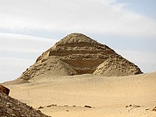 A photograph of the pyramid. The exterior consists of heaped layers of rubble draped over the stepped pyramid core. The stepped blocks protrude out from underneath.