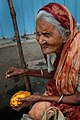 Old woman eating a mango, Dhaka.jpg