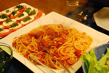 Spaghetti alla puttanesca, a spicy pasta dish topped with a sauce made of tomatoes, olives, anchovies and capers Pasta Puttanesca by koishikawagirl.jpg