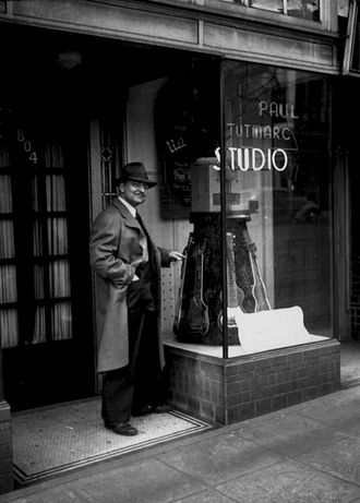 Bass guitar - Musical instrument inventor Paul Tutmarc outside his music store in Seattle, Washington