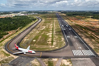 Eduardo Gomes International Airport - View of Eduardo Gomes International Airport's runway 10 (with TAM Airlines Airbus A330-200 holding short). Manaus city center is at the background.